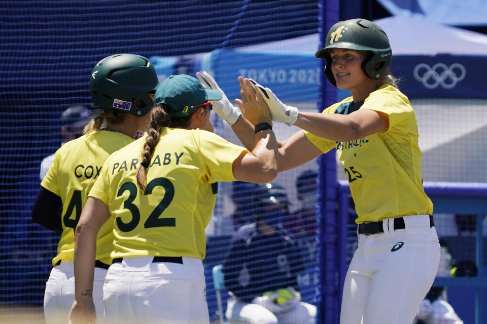 Australia's Chelsea Forkin (25) celebrates with teammates after scoring in the eighth inning of a softball game against United States at the 2020 Summer Olympics, Sunday, July 25, 2021, in Yokohama, Japan. (AP Photo/Sue Ogrocki)
