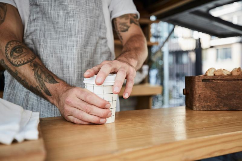 A barista serves up a coffee in a disposable cup.