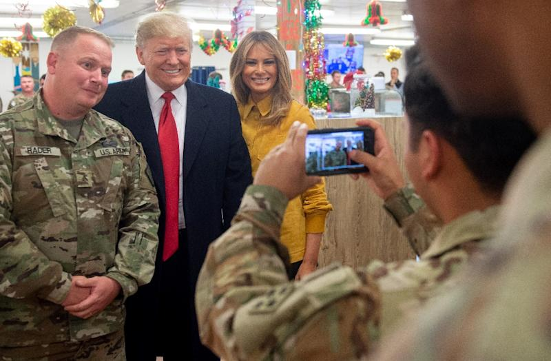 US President Donald Trump and First Lady Melania Trump pose for photos with members of the US military during an unannounced trip to Iraq on December 26, 2018 (AFP Photo/SAUL LOEB)