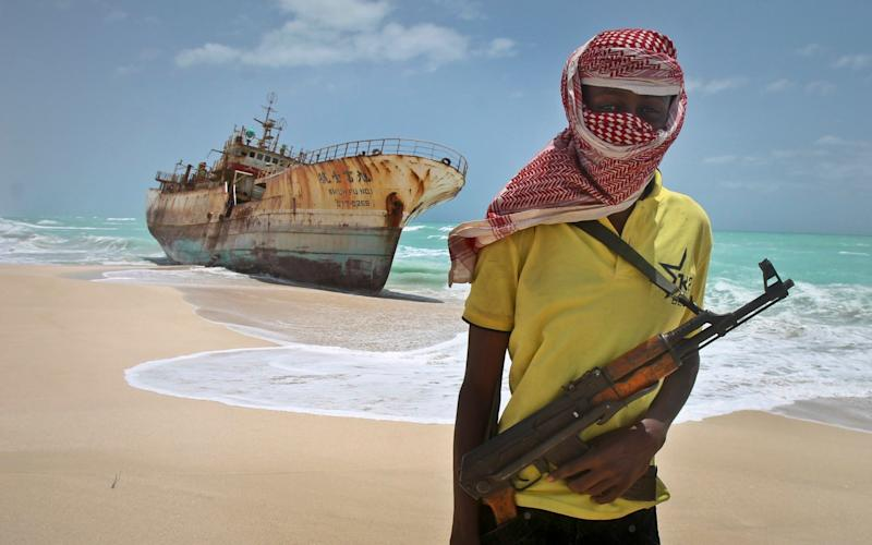 File image of a Somali pirate standing near a fishing vessel - AP