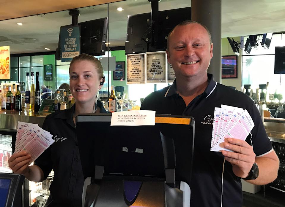 The winning $5.9 million entry was purchased at Cazalys sports bar in Cairns. Pictured are two staff members at the bar holding up Keno cards.