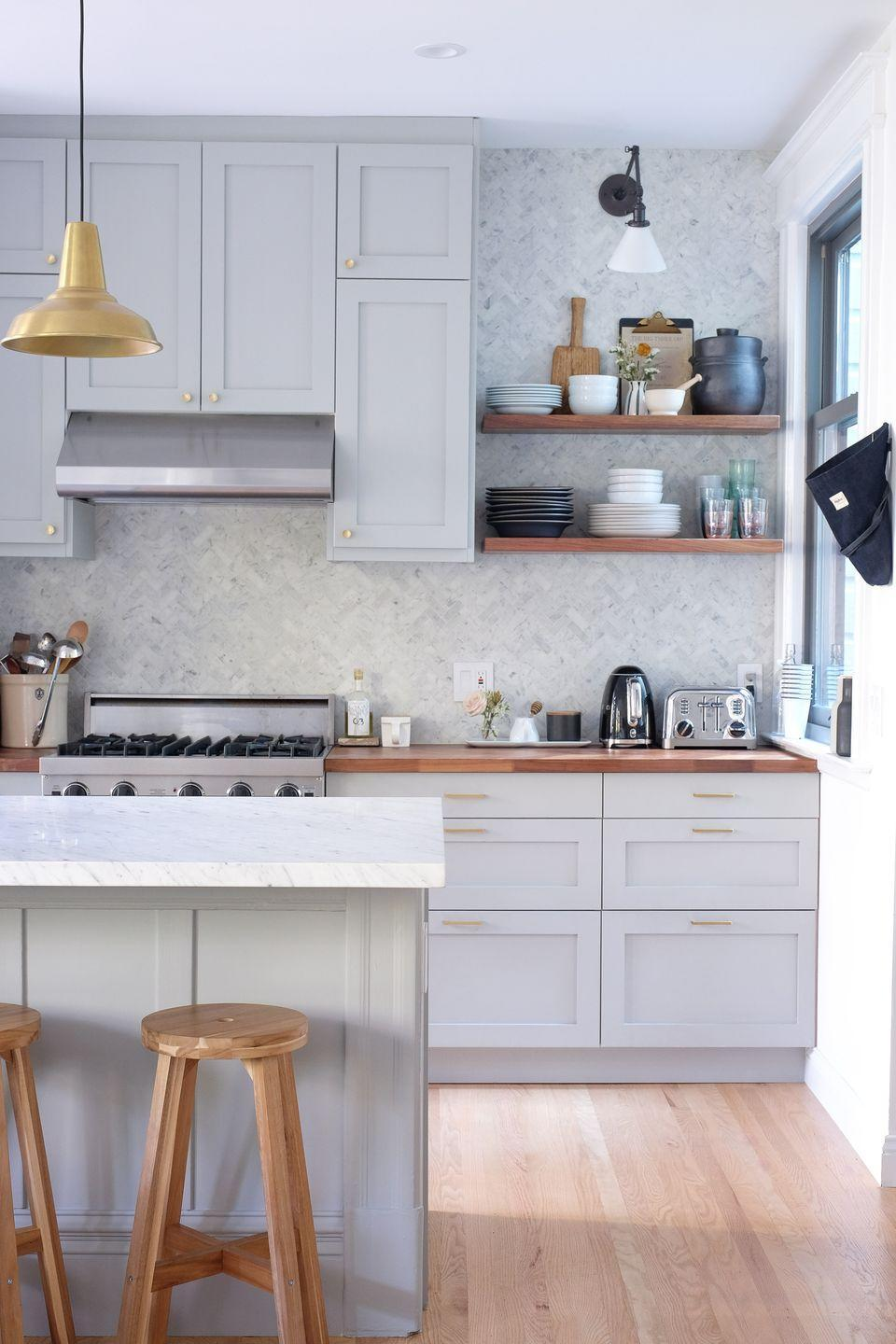 "<p>A warm gray cabinetry color, brass pendants, and multicolor tile on the backsplash of this IKEA kitchen by <a href=""https://ginarachelledesign.com/"" rel=""nofollow noopener"" target=""_blank"" data-ylk=""slk:Gina Rachelle Design"" class=""link rapid-noclick-resp"">Gina Rachelle Design</a> give it a feeling of timelessness. </p>"