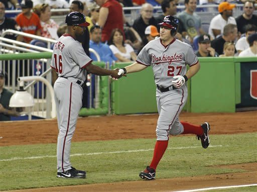 Washington Nationals' Jordan Zimmermann (27) is congratulated by third base coach Bo Porter (16) after hitting a solo home run in the third inning against the Miami Marlins during a baseball game at Marlins Park in Miami, on Monday, May 28, 2012. (AP Photo/Joel Auerbach)