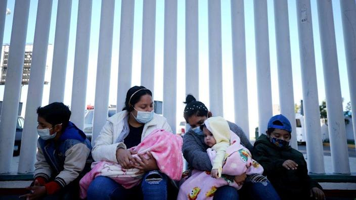 El Salvador and Honduras nationals seeking asylum in the United States sit outside the El Chaparral border crossing on February 19, 2021 in Tijuana, Mexico