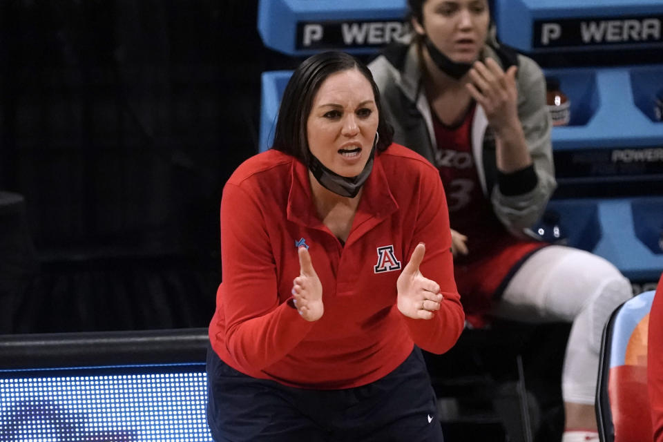 Arizona head coach Adia Barnes applauds her team during the first half of a women's Final Four NCAA college basketball tournament semifinal game against Connecticut Friday, April 2, 2021, at the Alamodome in San Antonio. (AP Photo/Morry Gash)