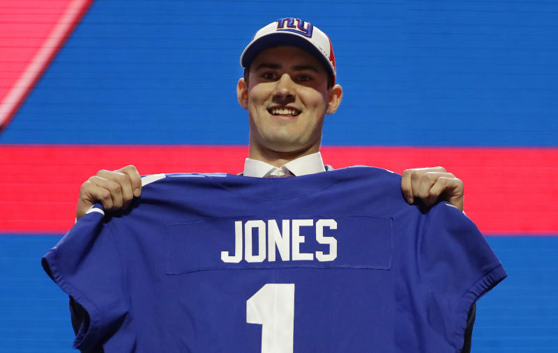 Duke quarterback Daniel Jones poses with his new jersey after the New York Giants selected Jones in the first round at the NFL football draft, Thursday, April 25, 2019, in Nashville, Tenn. (AP Photo/Mark Humphrey)