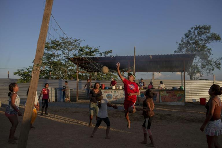 Young indigenous Warao people are seen playing outside a refugee shelter in Brazil's Roraima state