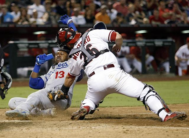 Los Angeles Dodgers shortstop Hanley Ramirez (13) slides home safely in front of Arizona Diamondbacks catcher Miguel Montero (26) in the seventh inning during a baseball game, Tuesday, Aug. 26, 2014, in Phoenix. (AP Photo/Rick Scuteri)