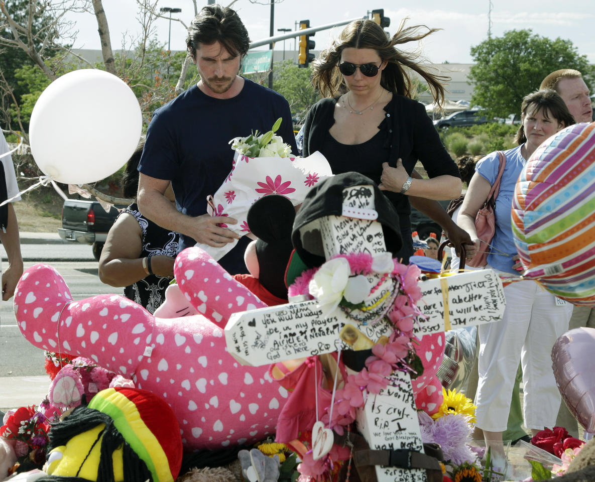"Actor Christian Bale and his wife Sibi Blazic view a cross and large display of flowers and stuffed animals dedicated to Veronica Moser-Sullivan, 6, the youngest of the 12 victims of Friday's mass shooting, Tuesday, July 24, 2012, at a memorial in Aurora, Colo. Twelve people were killed when a gunman opened fire during a late-night showing of the movie ""The Dark Knight Rises,"" which stars Bale as Batman. (AP Photo/Ted S. Warren)"