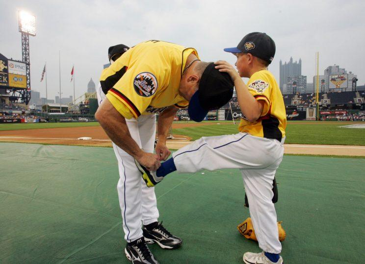 Tom Glavine ties Peyton Glavine's shoes before the 2006 Home Run Derby. Peyton is eligible for the MLB Draft in 2017. (AP Photo)