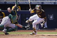 RETRANMISSION TO CORRECT LOCATION TO PEORIA - San Diego Padres' Jurickson Profar falls after being hit by a pitch in front of Oakland Athletics catcher Sean Murphy, left, in the first inning of a spring training baseball game Thursday, March 18, 2021, in Peoria, Ariz. (AP Photo/Sue Ogrocki)
