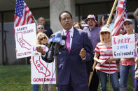"""FILE — In this July 13, 2021 file photo radio talk show host Larry Elder speaks to supporters during a campaign stop in Norwalk, Calif. Elder, in his first press conference since announcing his candidacy July 12, told reporters that if he replaces Democratic Gov. Gavin Newsom in the Sept. 14 election any mask or vaccine mandates in place at that time """"will be suspended right away."""" (AP Photo/Marcio Jose Sanchez, File)"""