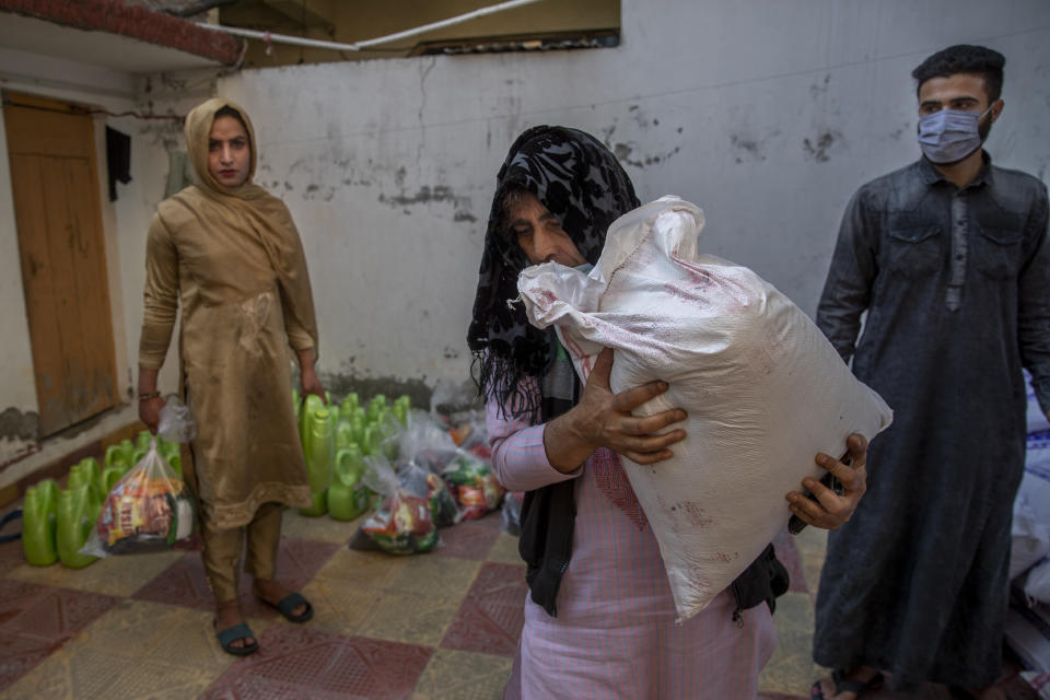 Bilal Ahmed, a transgender Kashmiri, carries a bag of rice distributed as food handout by a group in Srinagar, Indian controlled Kashmir, Thursday, May 27, 2021. Life has not been easy for many of Kashmir's transgender people. Most are ostracized by families and bullied in society. Living in the shadows of conflict, coupled with the recent crisis of the pandemic, pushed the community further to the margins. (AP Photo/ Dar Yasin)