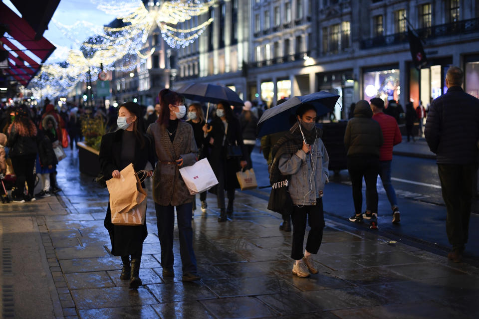Shoppers wear face masks as they walk in Regent Street, ahead of the new Tier-4 restriction measures, in London, Saturday, Dec. 19, 2020. Britain's Prime Minister Boris Johnson says Christmas gatherings cannot go ahead and non-essential shops must close in London and much of southern England as he imposed a new, higher level of coronavirus restrictions to curb rapidly spreading infections.(AP Photo/Alberto Pezzali)