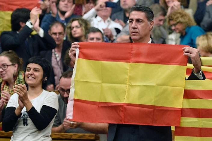 Popular Party of Catalonia (PPC) leader Xavier Garcia Albiol holds up a Spanish flag following the vote on a proposed resolution to secede from the rest of the country, during a session at the Catalan Parliament in Barcelona, on November 9, 2015 (AFP Photo/Lluis Gene)
