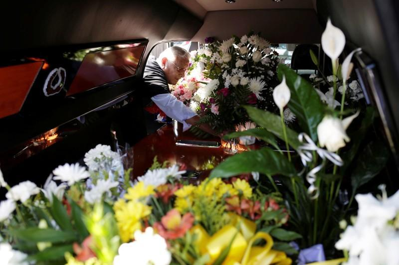 A man puts flowers inside a hearse of one of the victims of a mass shooting at a Walmart store during a tribute in El Paso