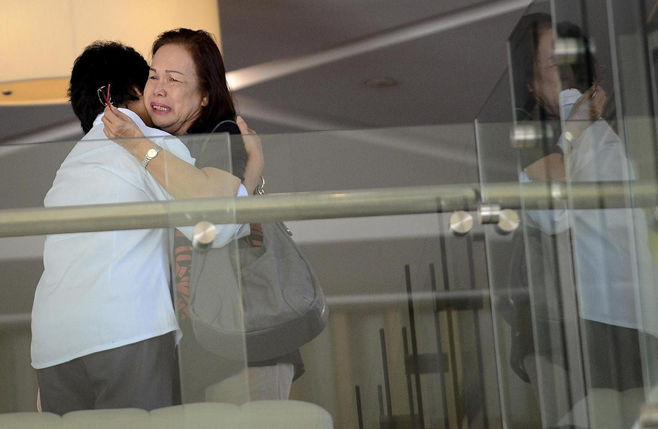 Family members of passengers aboard a missing plane cry at a hotel in Putrajaya, Malaysia, Sunday, March 9, 2014. Military radar indicates that the missing Boeing 777 jet of Malaysia Airlines may have turned back, Malaysia's air force chief said Sunday as scores of ships and aircraft from across Asia resumed a hunt for the plane and its 239 passengers. (AP Photo) MALAYSIA OUT