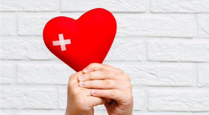 Image of hands holding a red heart with a patch on it and a background comprised of white bricks