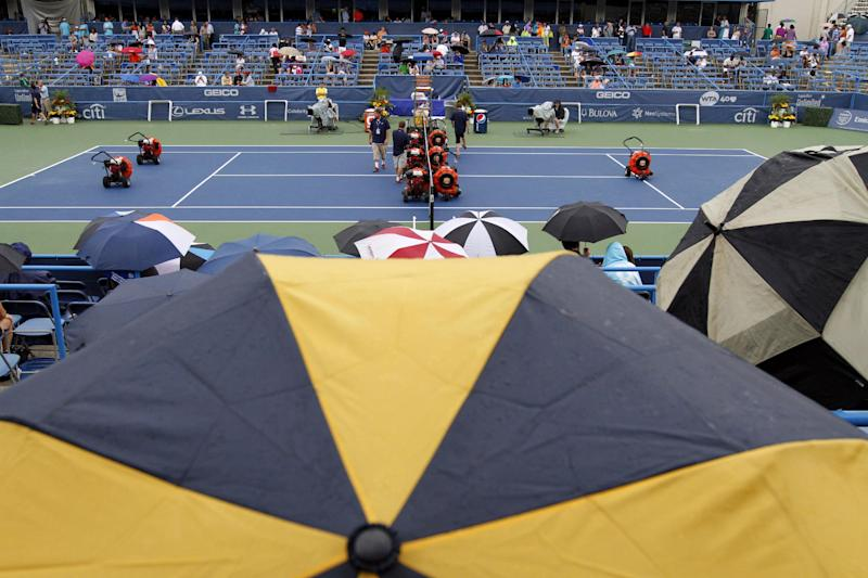 Umbrellas are in use during a rain delay in the match between Dmitry Tursunov, from Russia, and John Isner at the Citi Open tennis tournament, Saturday, Aug. 3, 2013 in Washington. (AP Photo/Alex Brandon)
