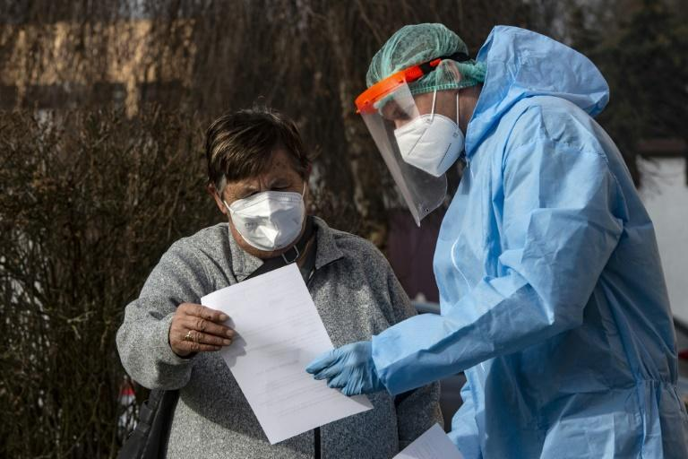 A Czech soldier wearing protective equipment (PPE) shows the results of a coronavirus test to a patient in Chodova Plana town, western Bohemia