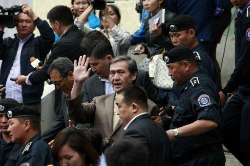 Former Mongolian leader Nambar Enkhbayar (C) waves as he leaves court in Ulan Bator in June 2012. On Thursday, a Mongolian court found him guilty of misappropriating gifts intended for a monastery, along with other corruption charges, in a hearing broadcast to the nation
