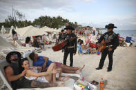 """Roving musicians """"Los Compas"""" approach a group of tourists on the shore of Mamitas beach, in Playa del Carmen, Quintana Roo state, Mexico, Tuesday, Jan. 5, 2021, amid the new coronavirus pandemic. Tens of thousands of American tourists descended on Mexico's glittering Caribbean beaches at the close of 2020 and the start of 2021, taking a break from the pandemic winter in the United States. (AP Photo/Emilio Espejel)"""
