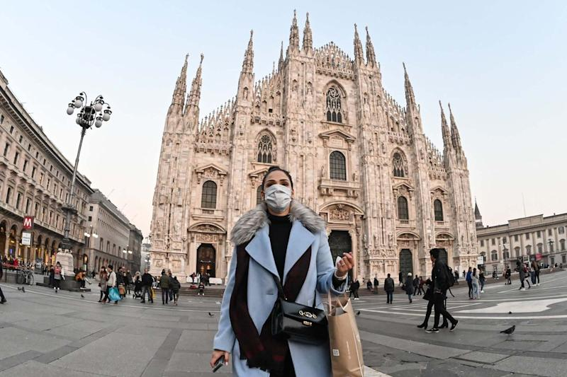 A woman with a protective face mask in front of the Duomo in Milan (AFP via Getty Images)