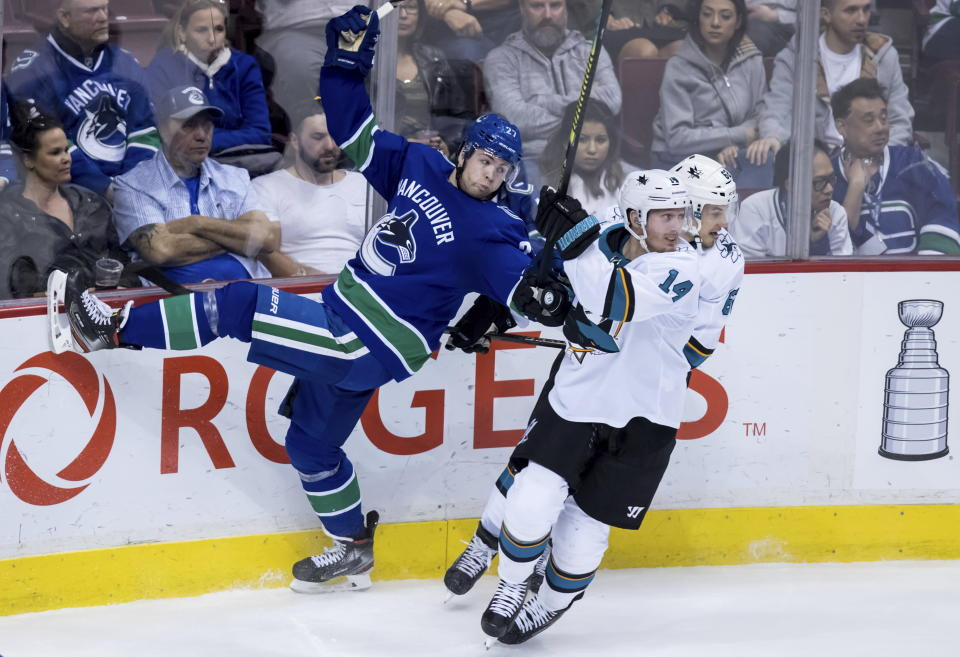 Vancouver Canucks' Ben Hutton, left, collides with San Jose Sharks' Gustav Nyquist, front right, of Sweden, and Kevin Labanc during the second period of an NHL hockey game in Vancouver, British Columbia, Tuesday April 2, 2019. (Darryl Dyck/The Canadian Press via AP)