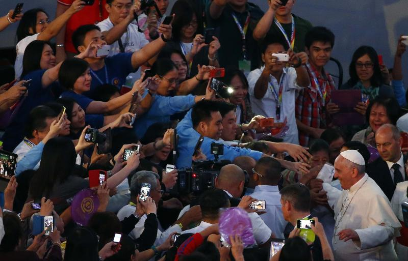 Pope Francis waves to the Catholic faithful as he arrives for a meeting with Filipino families in Manila