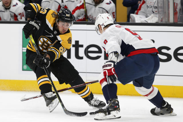 Washington Capitals' Dmitry Orlov (9) defends against Boston Bruins' Brad Marchand (63) during the first period of an NHL hockey game in Boston, Saturday, Nov. 16, 2019. (AP Photo/Michael Dwyer)