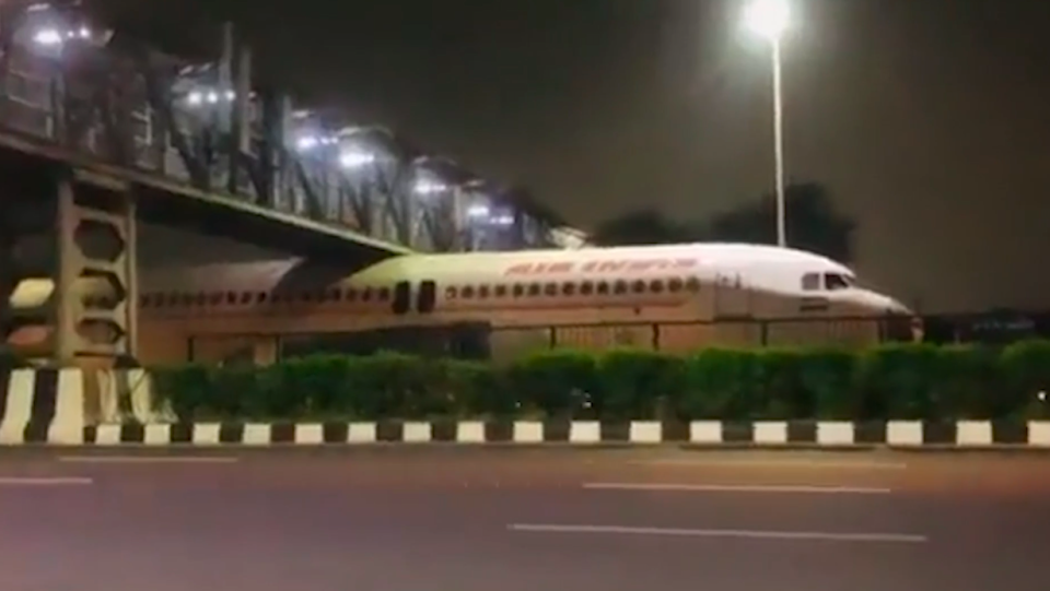 Footage shows the nose of the aircraft and only half of its body had made it under the iron footbridge in India. (SWNS)