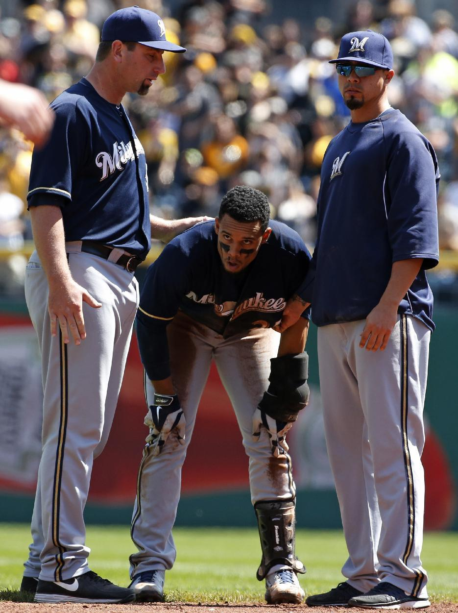 Milwaukee Brewers' Carlos Gomez, center, catches his breath after participating in a brawl with the Pittsburgh Pirates during the third inning of a baseball game in Pittsburgh, Sunday, April 20, 2014. Gomez and Pirates' Travis Snider were ejected from the game. (AP Photo/Gene J. Puskar)
