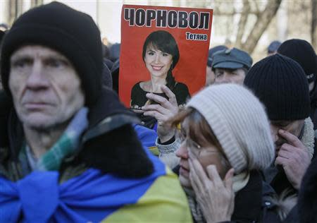 A protester holds a picture of journalist Tetyana Chornovil, who was beaten and left in a ditch just hours after publishing an article on the assets of top government officials, during a protest rally in front of the Ukrainian Ministry of Internal Affairs in Kiev December 26, 2013. REUTERS/Gleb Garanich