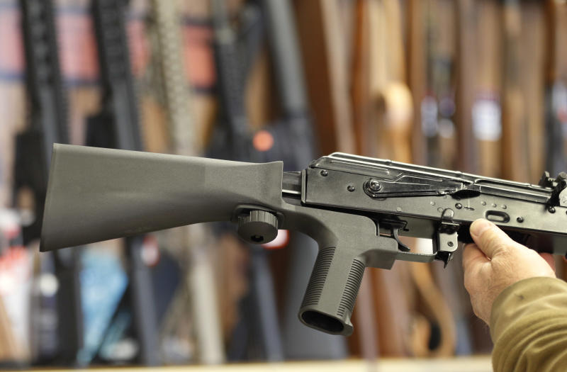 A bump stock device (left) fits on a semi-automatic rifle to increase the firing speed, making it similar to a fully automatic rifle. (George Frey via Getty Images)