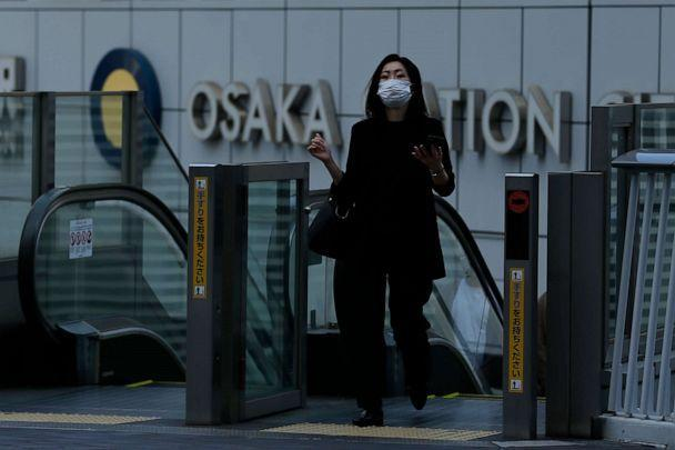 PHOTO: A woman wearing a face mask to protect against COVID-19 walks out of Osaka Station in Osaka, Japan, on April 23, 2021. (Buddhika Weerasinghe/Getty Images)