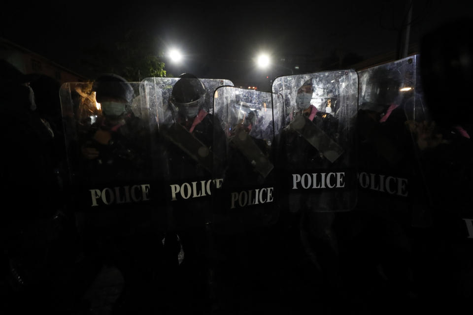 Police hold shields in tight formation as pro-democracy protesters march demanding the release of pro-democracy activists in Bangkok, Thailand, Wednesday, Feb. 10, 2021. Protesters demanded the government to step down, the constitution to be amended to make it more democratic and the monarchy be more accountable. (AP Photo/Sakchai Lalit)