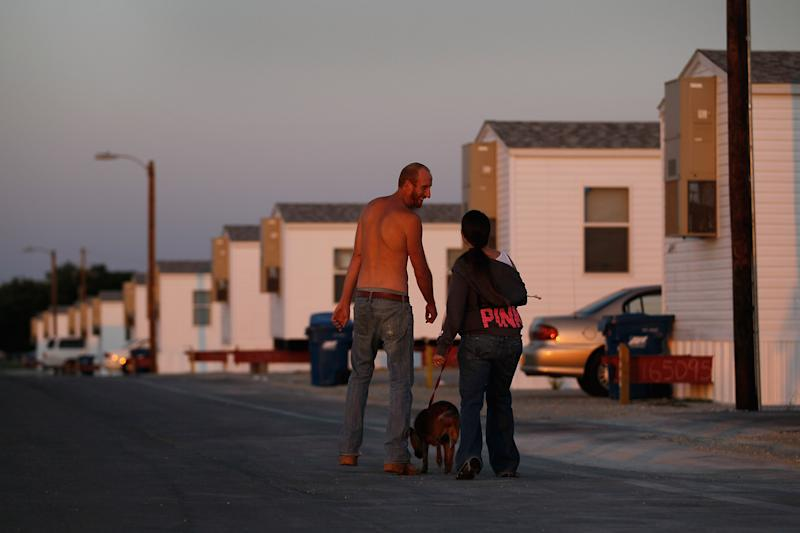 JOPLIN, MO - MAY 22: Levi Welde (L) walks with his friend Krystal Barnes in the FEMA trailer park that she lives in after her home was destroyed when a tornado hit the city one year ago on May 22, 2012 in Joplin, Missouri. Today marked the one-year anniversary of the EF-5 tornado that devastated the town leaving behind a path of destruction along with 161 deaths and hundreds of injuries, but one year later people continue to move out of the temporary FEMA housing sites and into permanent homes. (Photo by Joe Raedle/Getty Images)