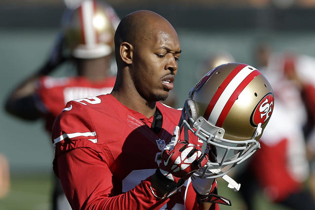 FILE - In this Jan. 15, 2014 file photo, San Francisco 49ers cornerback Carlos Rogers adjusts his helmet during practice at an NFL football training facility in Santa Clara, Calif. Ten former NFL players have been charged with defrauding the leagues healthcare benefit program. They include five who played on the Washington Redskins, including Clinton Portis and Carlos Rogers. (AP Photo/Jeff Chiu)