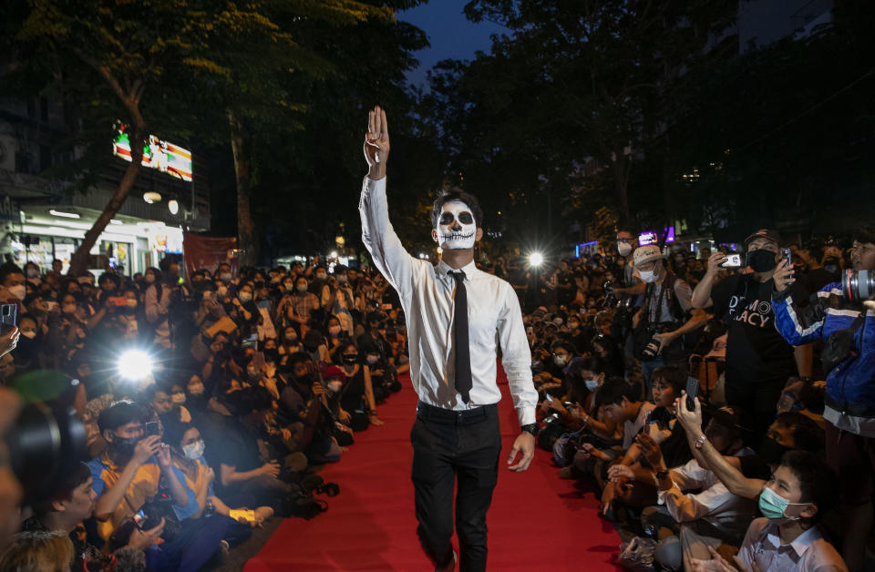 "Pro-democracy protesters perform on a mock ""red carpet"" fashion show billed as a counterpoint to a fashion show being held by one of the monarchy's princesses nearby in Bangkok, Thailand, Thursday, Oct. 29, 2020. The protesters continued to gather Thursday, led by their three main demands of Prime Minister Prayuth Chan-ocha's resignation, changes to a constitution that was drafted under military rule and reforms to the constitutional monarchy. (AP Photo/Gemunu Amarasinghe)"