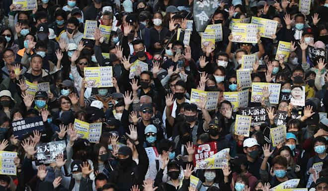 Marchers in Causeway Bay hold out their hands in a symbol of their five demands. Photo: Robert Ng