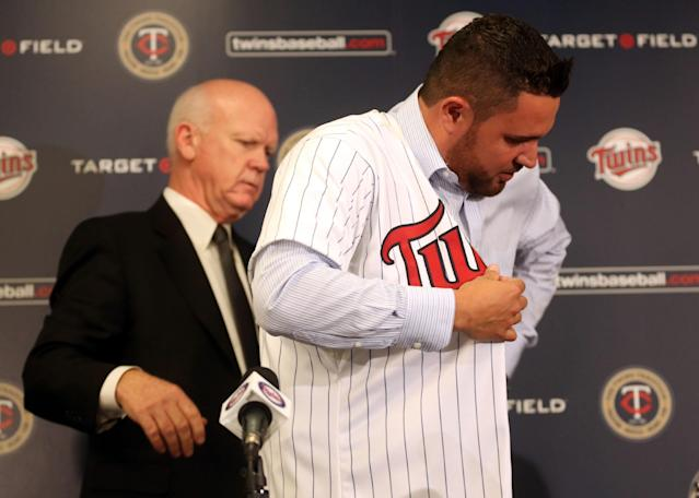 Twins general manager Terry Ryan helps free-agent Ricky Nolasco with his new jersey during a news conference at Target Field in Minneapolis, Tuesday, Dec. 3, 2013. The Twins have finalized a $49 million, four-year contract with right-hander Nolasco. (AP Photo/The Star Tribune, Kyndell Harkness)