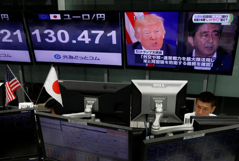An employee of a foreign exchange trading company works near a monitor showing Japan's Prime Minister Shinzo Abe and U.S. President Donald Trump in a television news report about their telephone conference on North Korea's threat in Tokyo, Japan September 4, 2017. REUTERS/Issei Kato