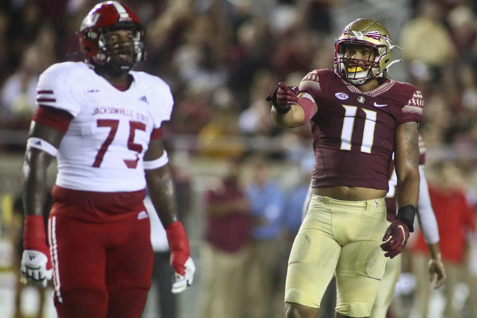At right, Florida State defensive end Jermaine Johnson II (11) points to Jacksonville State offensive lineman Ye'Majesty Sanders (75) after he committed a false start penalty in the first quarter of an NCAA college football game Saturday, Sept. 11, 2021, in Tallahassee, Fla. (AP Photo/Phil Sears)
