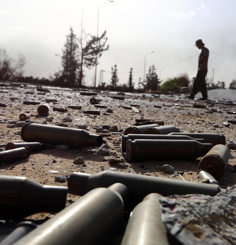 Spent bullet shells litter the ground as a member of the Islamist-linked militia of Misrata walks past following three days of battles in the area of Tripoli's International airport, on August 21, 2014