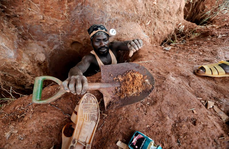 FILE PHOTO: An informal gold miner carries a shovel as he climbs out from inside a gold mining pit at the site of Nsuaem-Top