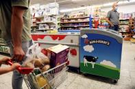 Customers walk near a refrigerator bearing the Ben & Jerry's logo at a food store in the Jewish settlement of Efrat in the Israeli-occupied West Bank