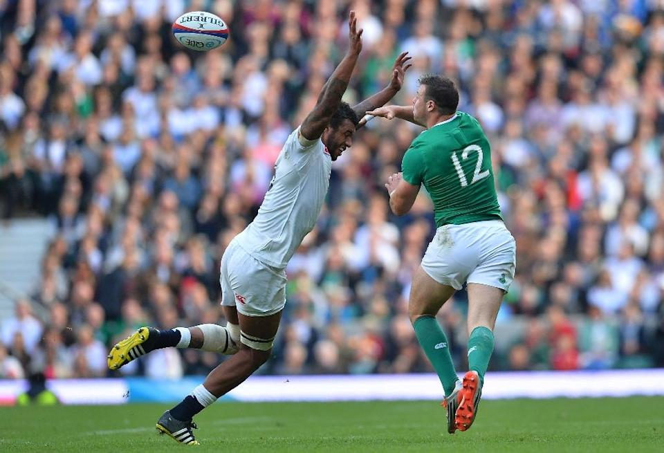 Ireland's Robbie Henshaw passes the ball under pressure from England's Courtney Lawes during the match ahead of the 2015 Rugby World Cup, at Twickenham Stadium, west of London, on September 5, 2015 (AFP Photo/Glyn Kirk)