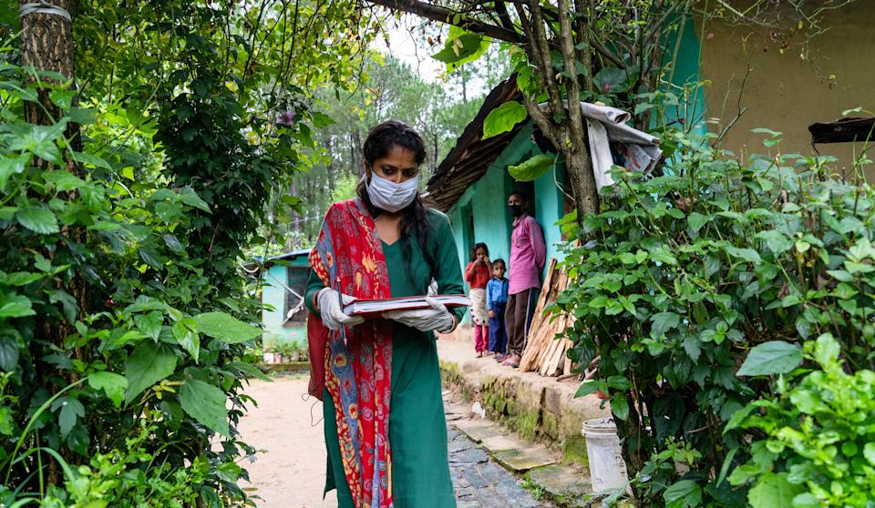 Kamla Devi, an ASHA worker in Palampur, checking people for COVID and TB symptoms.
