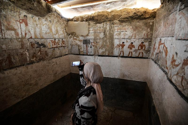 A woman takes a photo inside the newly discovered tomb of Old Kingdom official Hetpet who was priestess to fertility goddess Hathor on Egypt's Giza plateau (AFP Photo/MOHAMED EL-SHAHED)