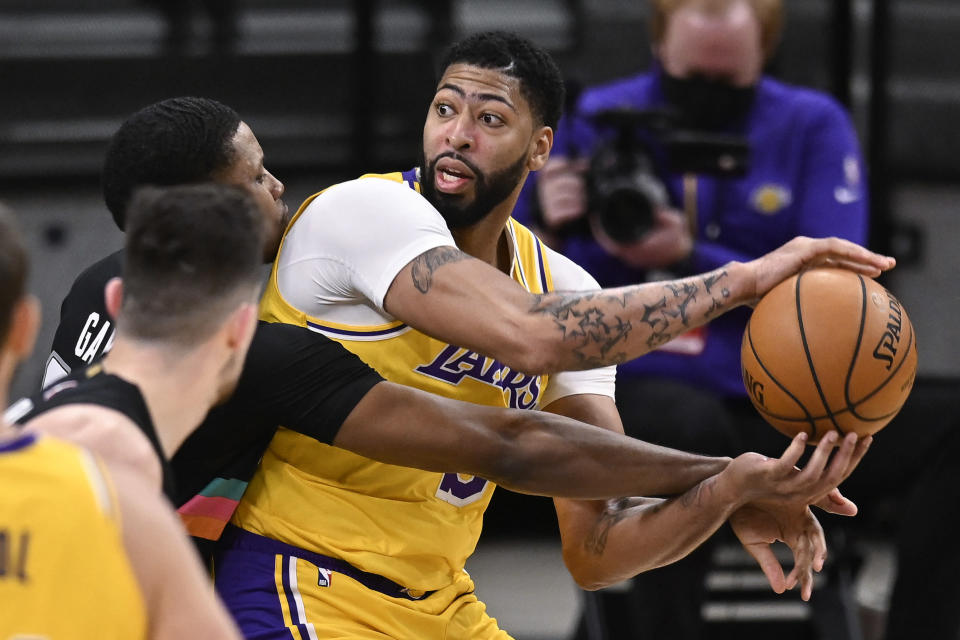 Los Angeles Lakers' Anthony Davis, right, keeps the ball from San Antonio Spurs' Rudy Gay, left rear, and Drew Eubanks during the first half of an NBA basketball game Friday, Jan. 1, 2021, in San Antonio. (AP Photo/Darren Abate)